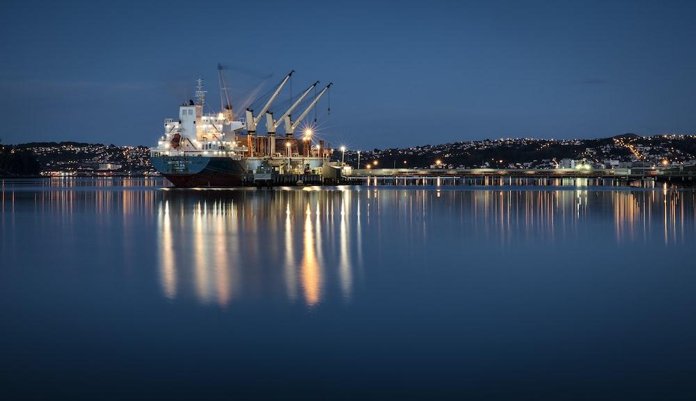 white and blue cargo ship near dock under blue sky