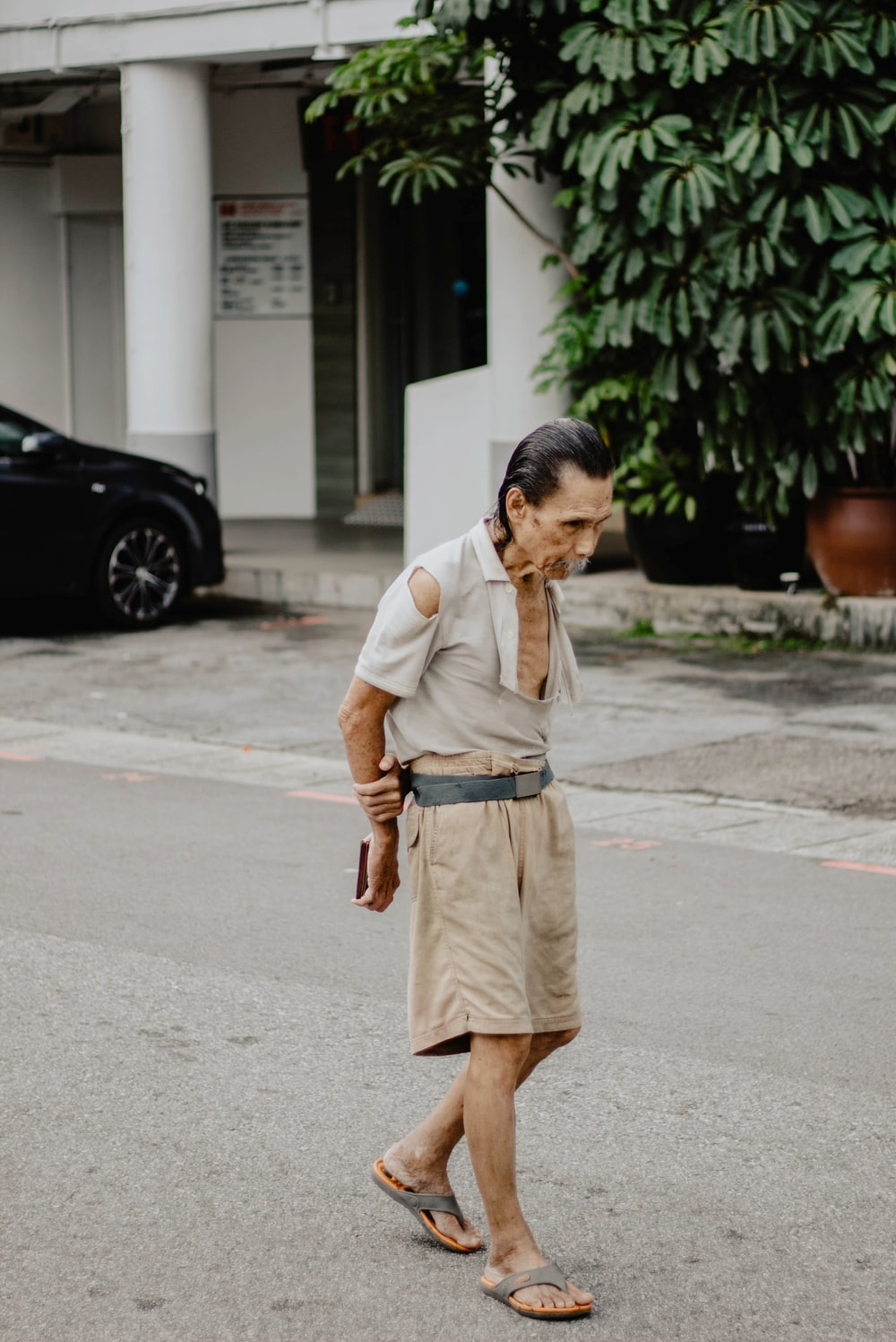 man wearing brown shorts standing on concrete road