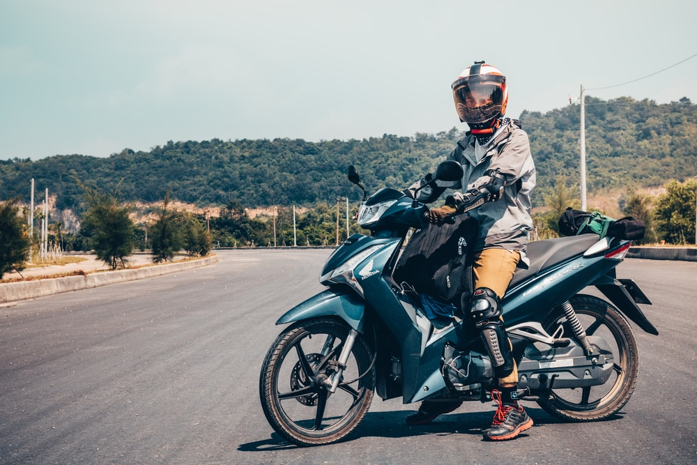 man riding on green underbone motorcycle