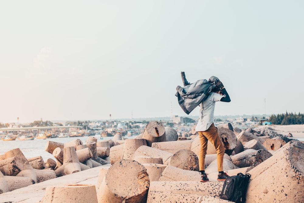 man carrying jacket on rocks