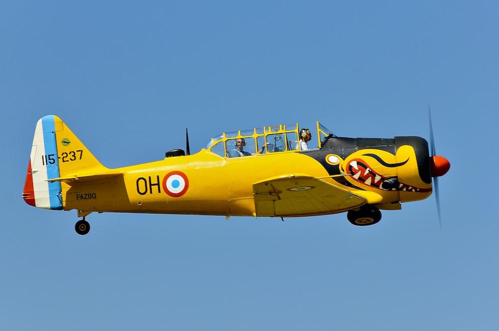 two men riding in yellow plane