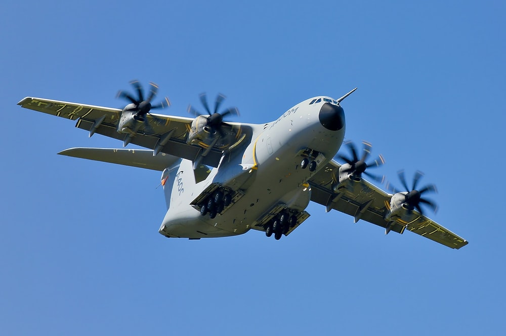 grey military cargo plane on flight under clear blue sky