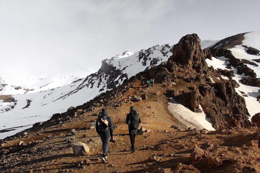 two man climbing mountain