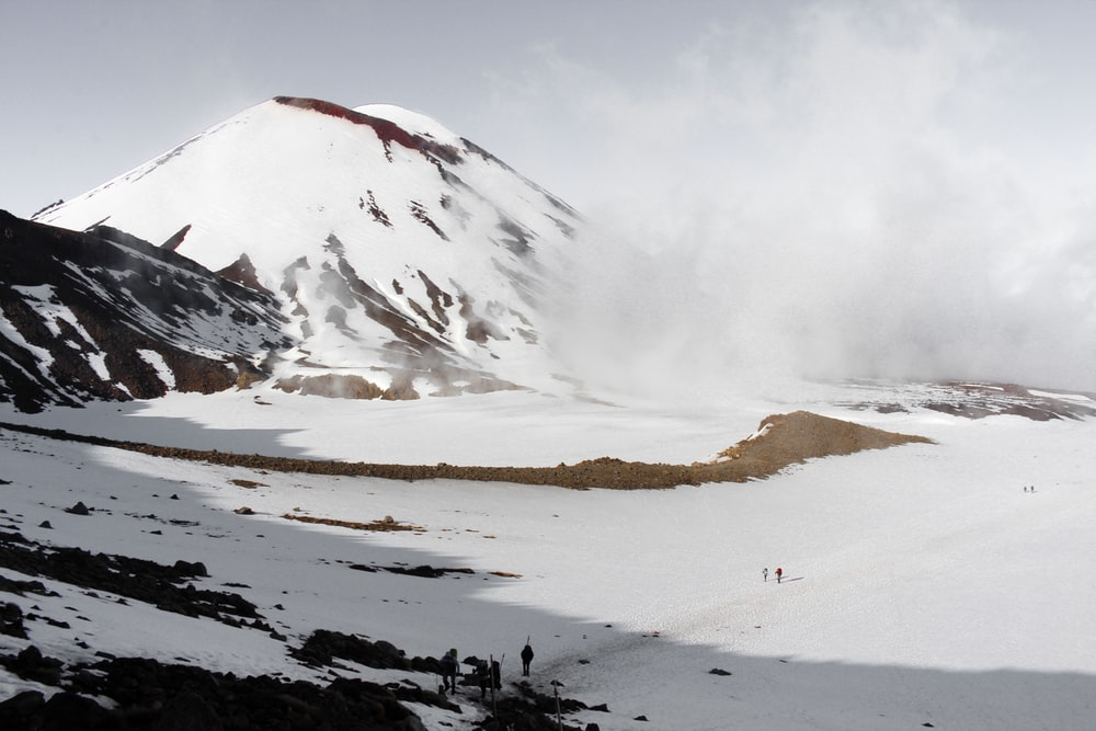 people walking on field near snow covered hill during daytime