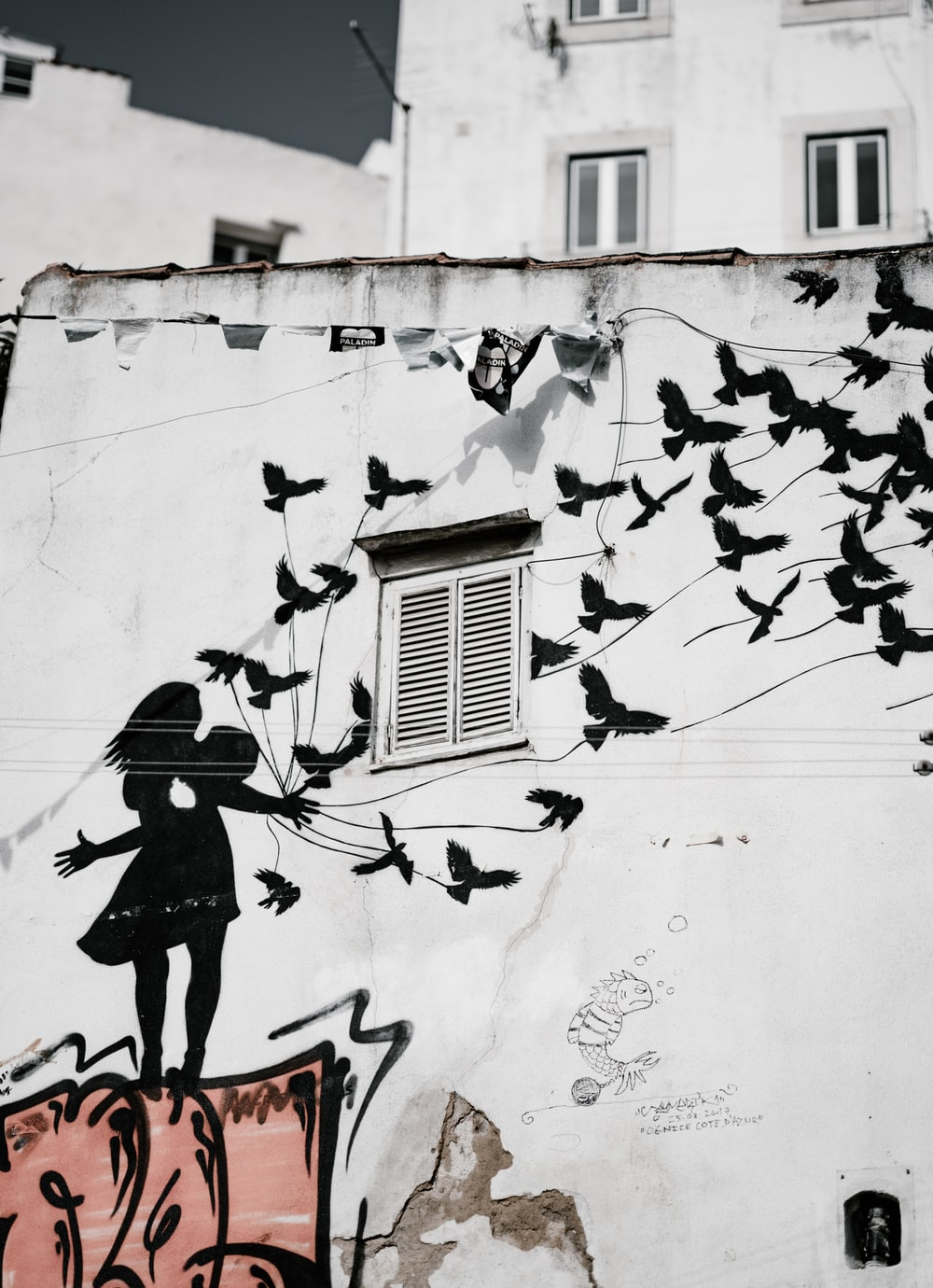 man and woman kissing each other with flight of bird graffiti