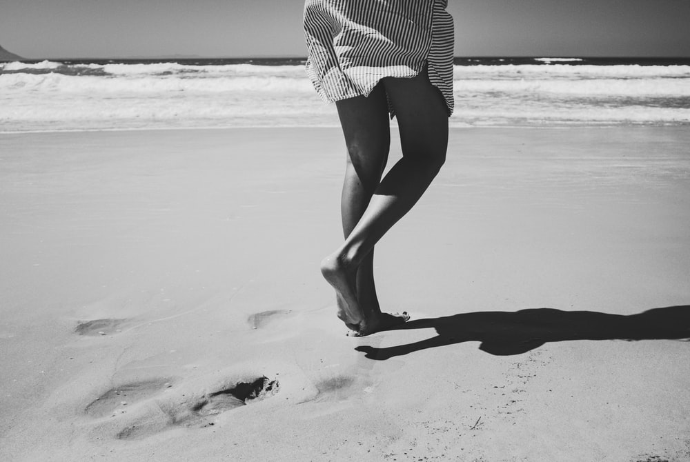 person walking on beach grayscale photography