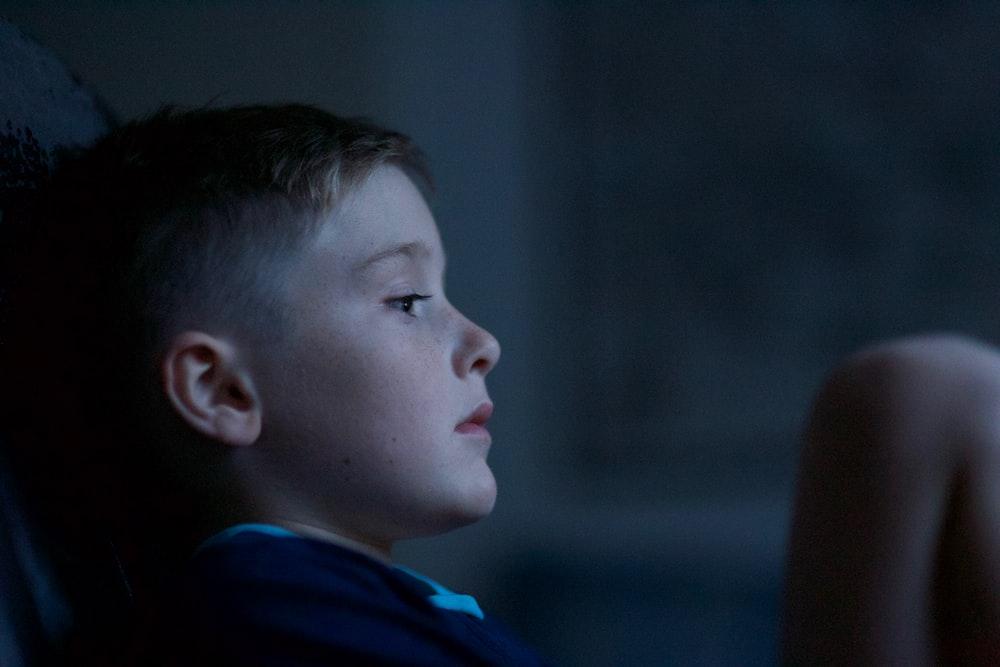 boy leaning on black wall
