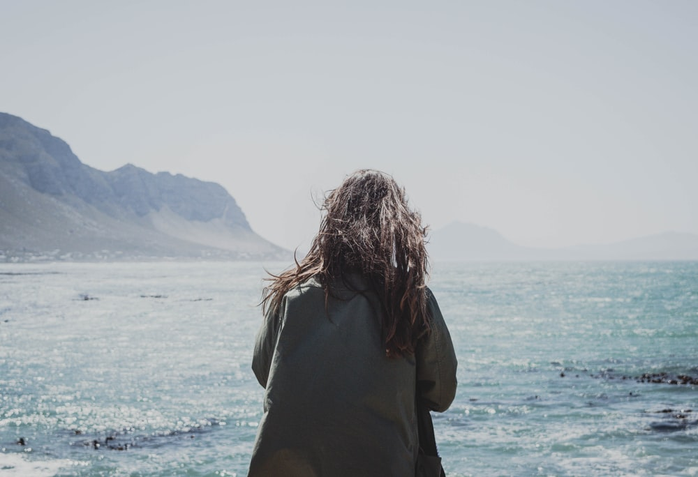 woman standing infront of body of water