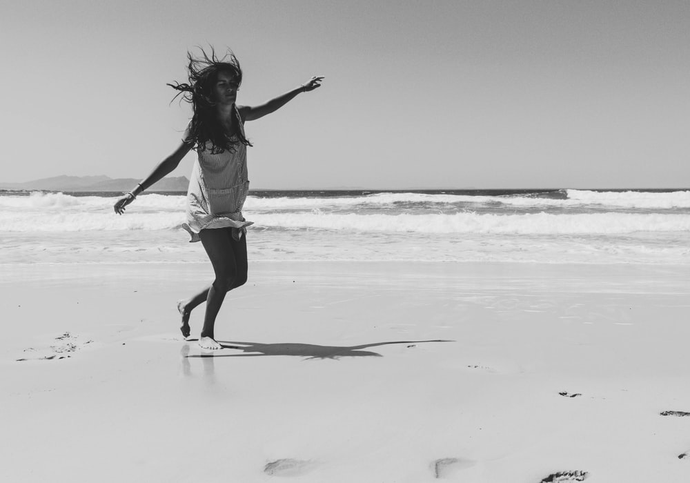 grayscale photo of woman walking in seashore