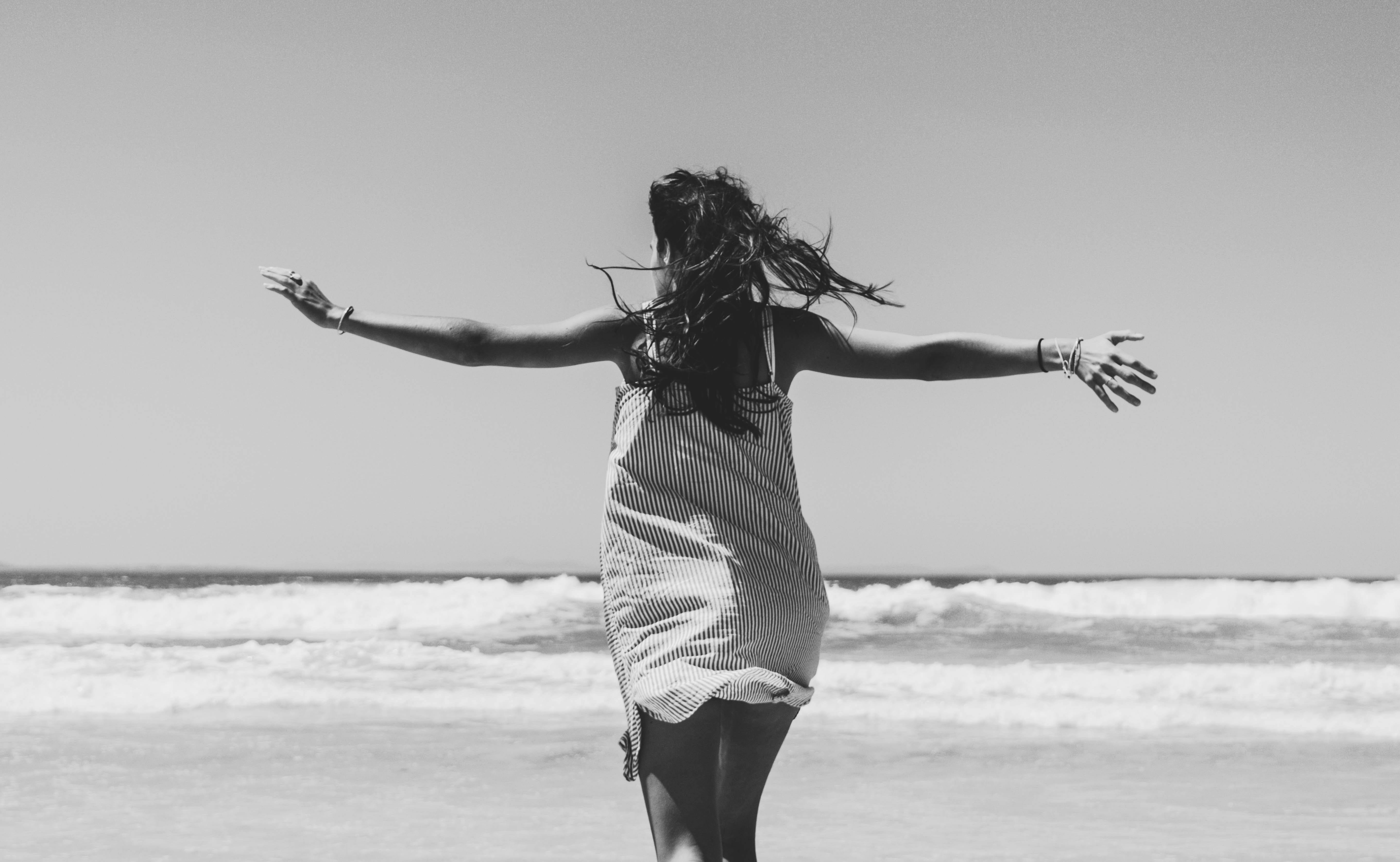 woman standing facing beach with arms wide open