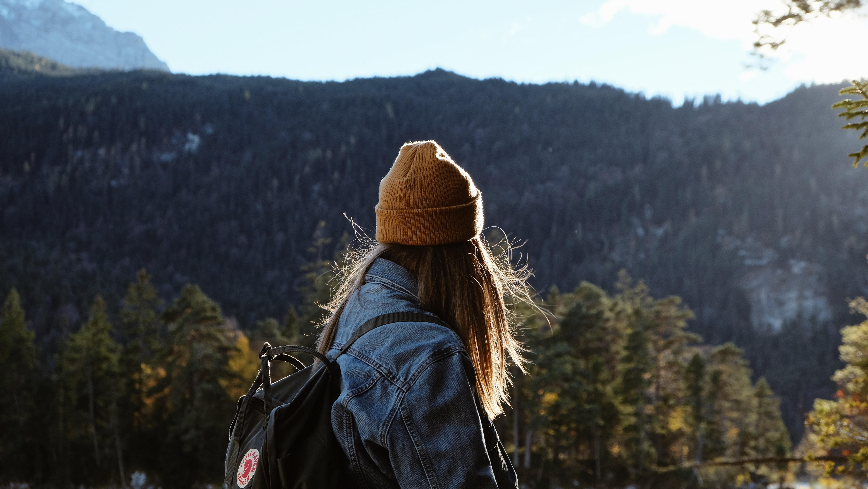woman wearing blue denim jacket overlooking green forest