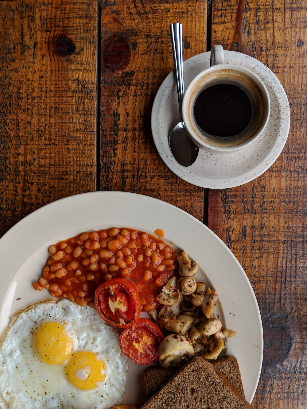 black coffee near sunny side up egg with sliced tomatoes, mushroom and bread on plate