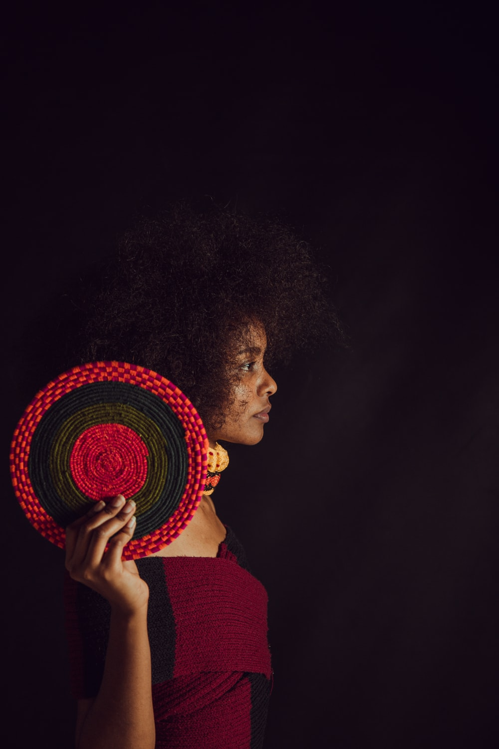woman wearing maroon and black top holding round black and red decor