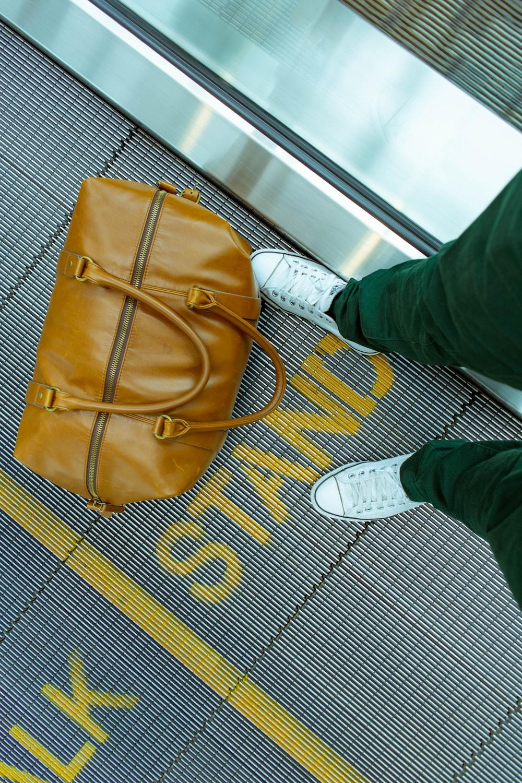 person stranding beside brown leather handbag