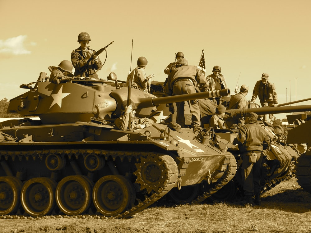 people sitting and standing on battle tank
