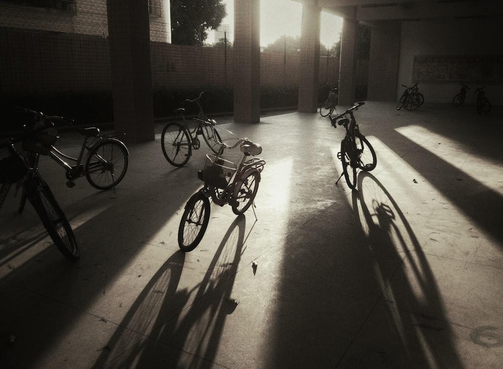 four black bikes near post during daytime