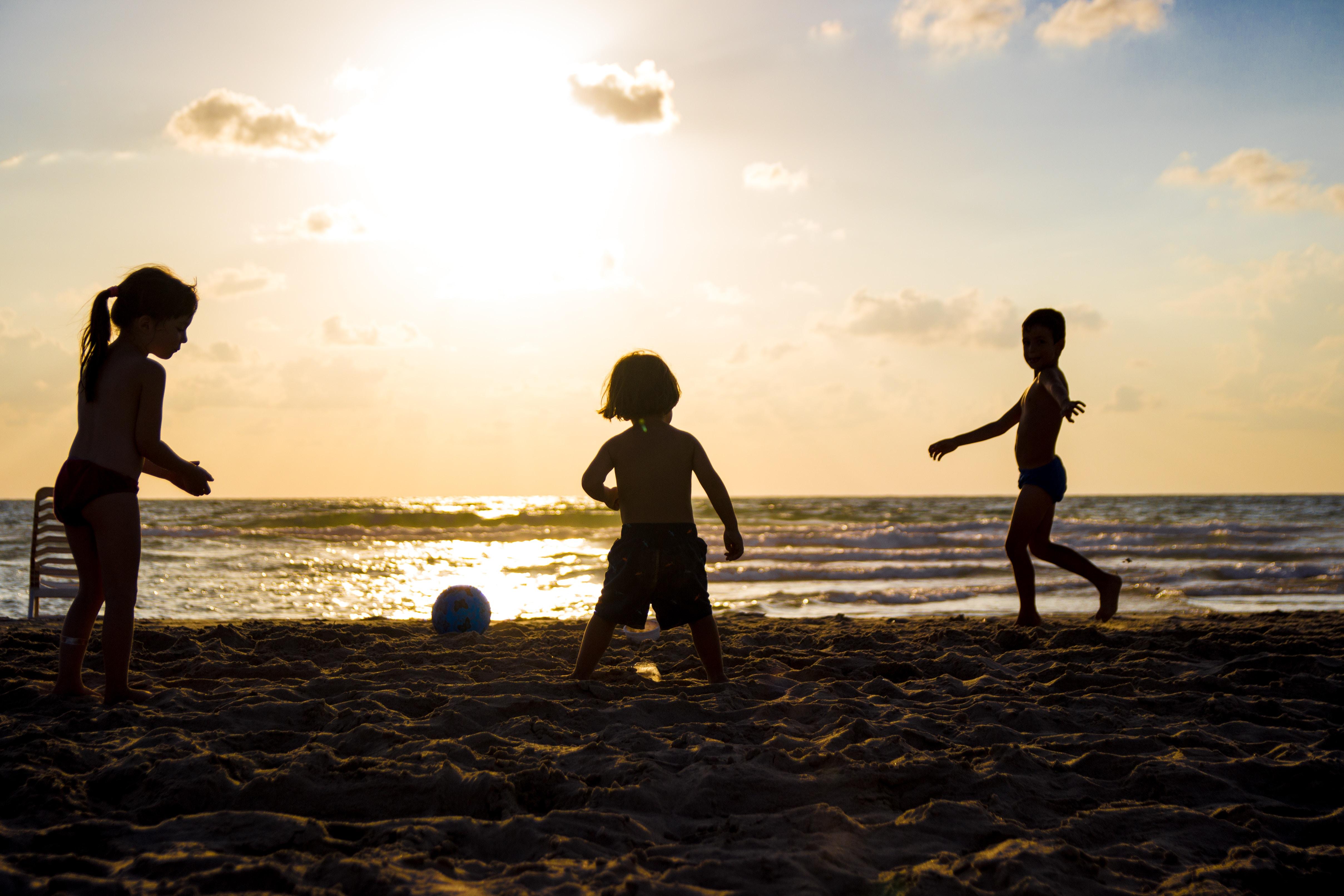 silhouette of three children on beach