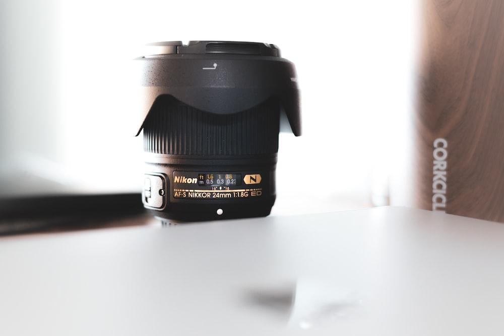 black Nikon camera zoom lens on table