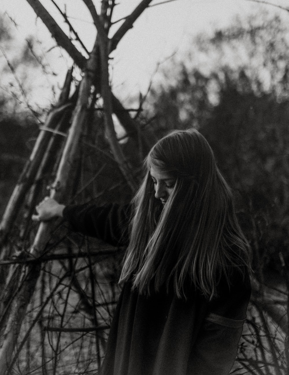grayscale photography of woman wearing wooden post