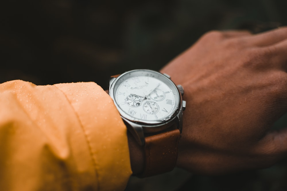 person wearing round silver-colored chronograph watch