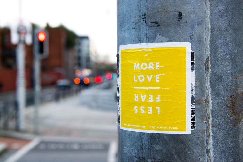 more love less fear sticker on post