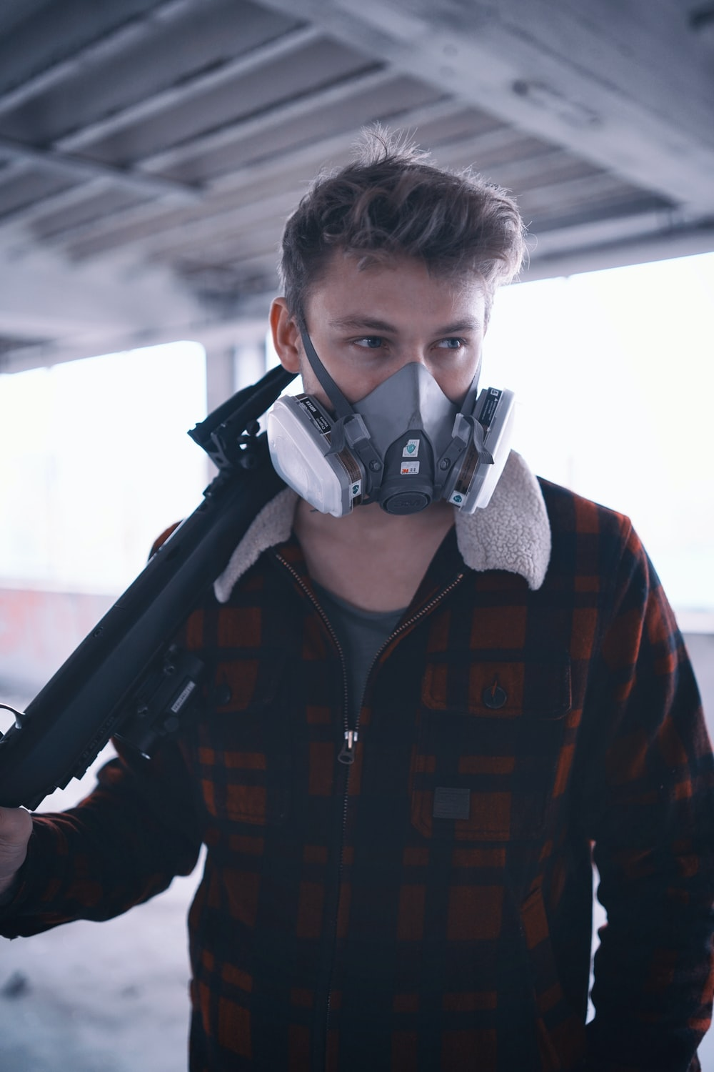 man in maroon plaid coat wearing protective mask