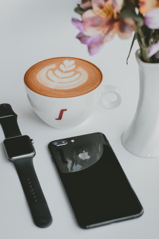 black iPhone 8 beside Apple watch