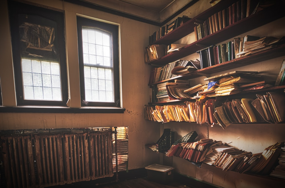 assorted books on rack near glass window