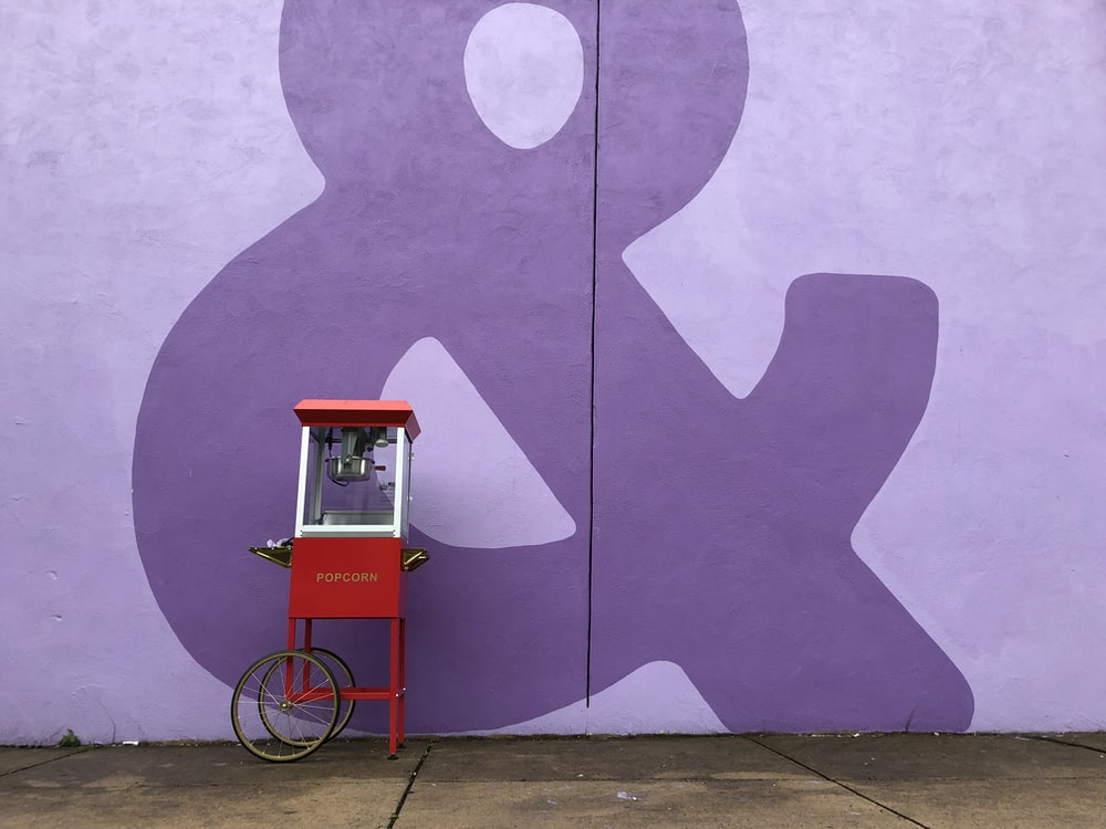 red and white popcorn cart beside purple wall