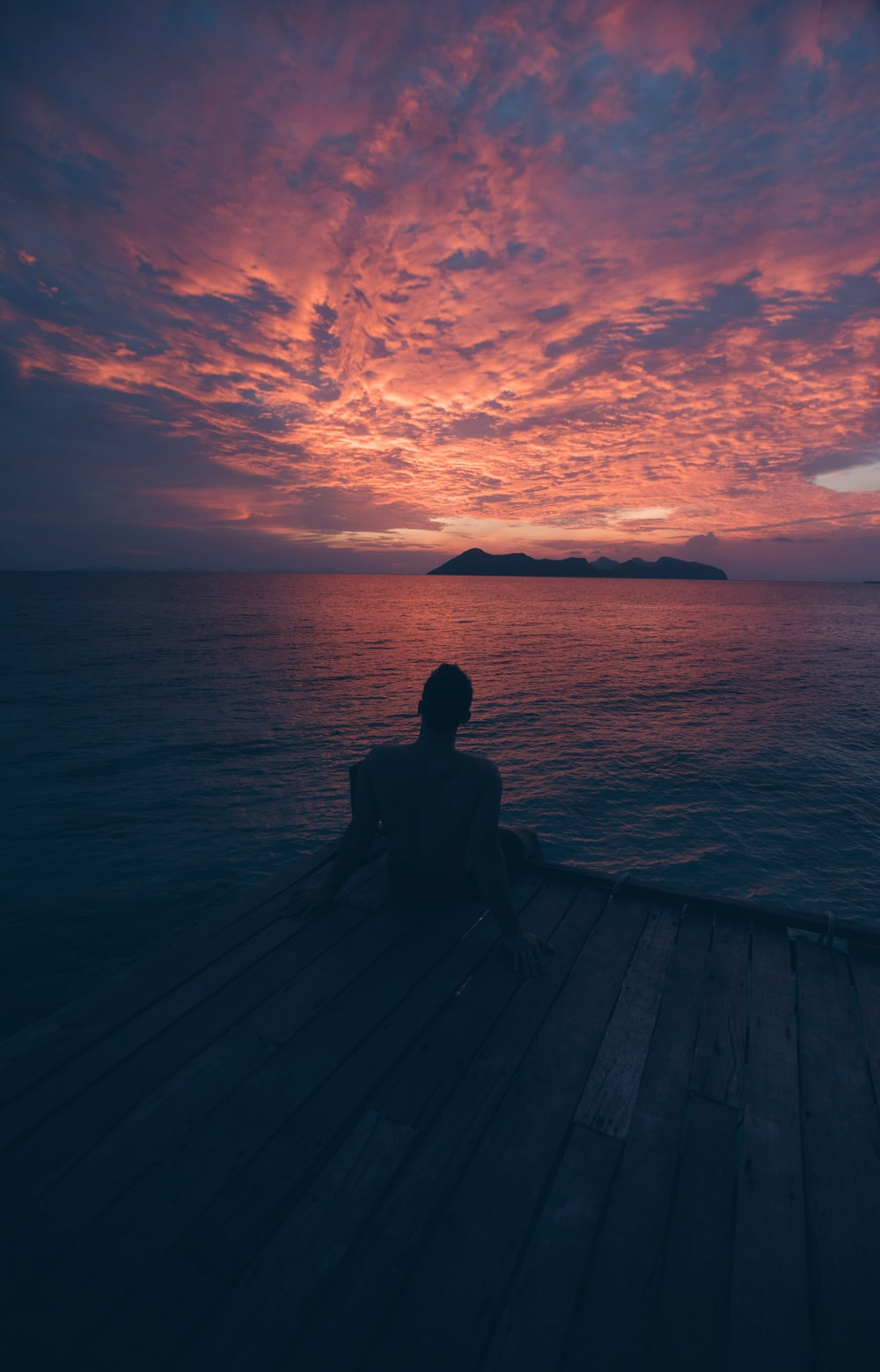 person sitting on beach dock during sunset