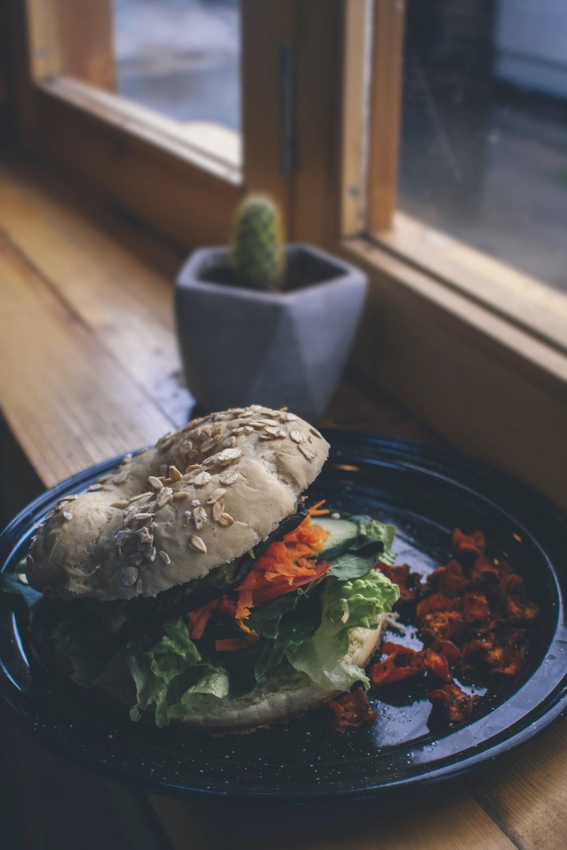 burger on black plate beside purple ceramic vase