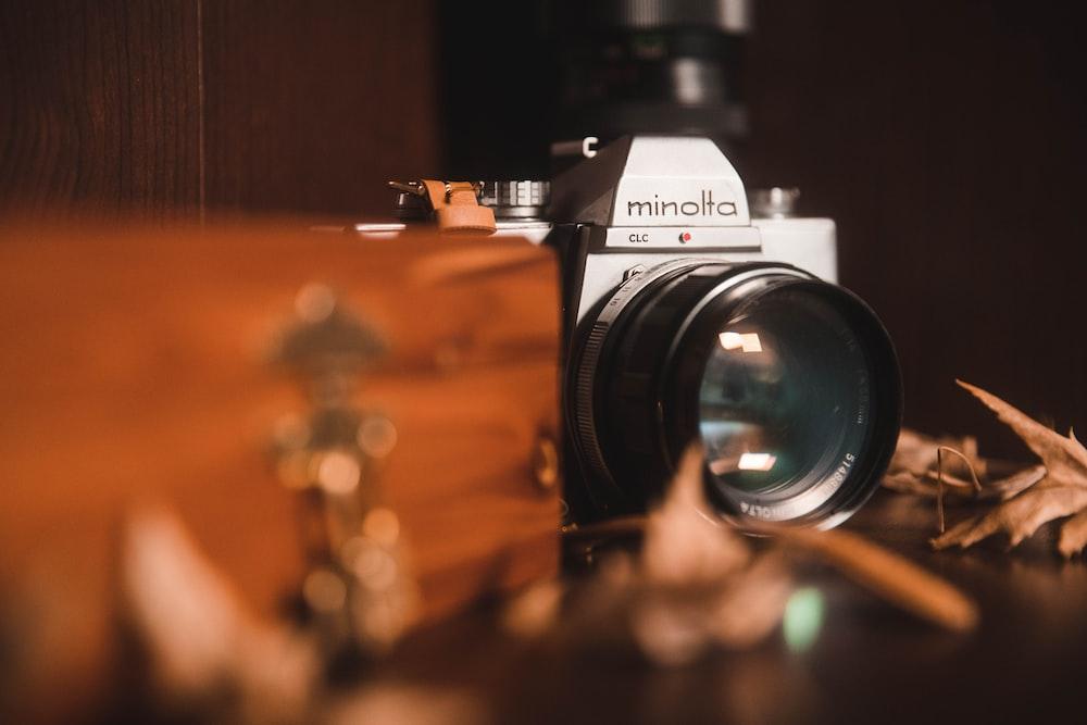 gray Minolta DSLR camera near brown surface