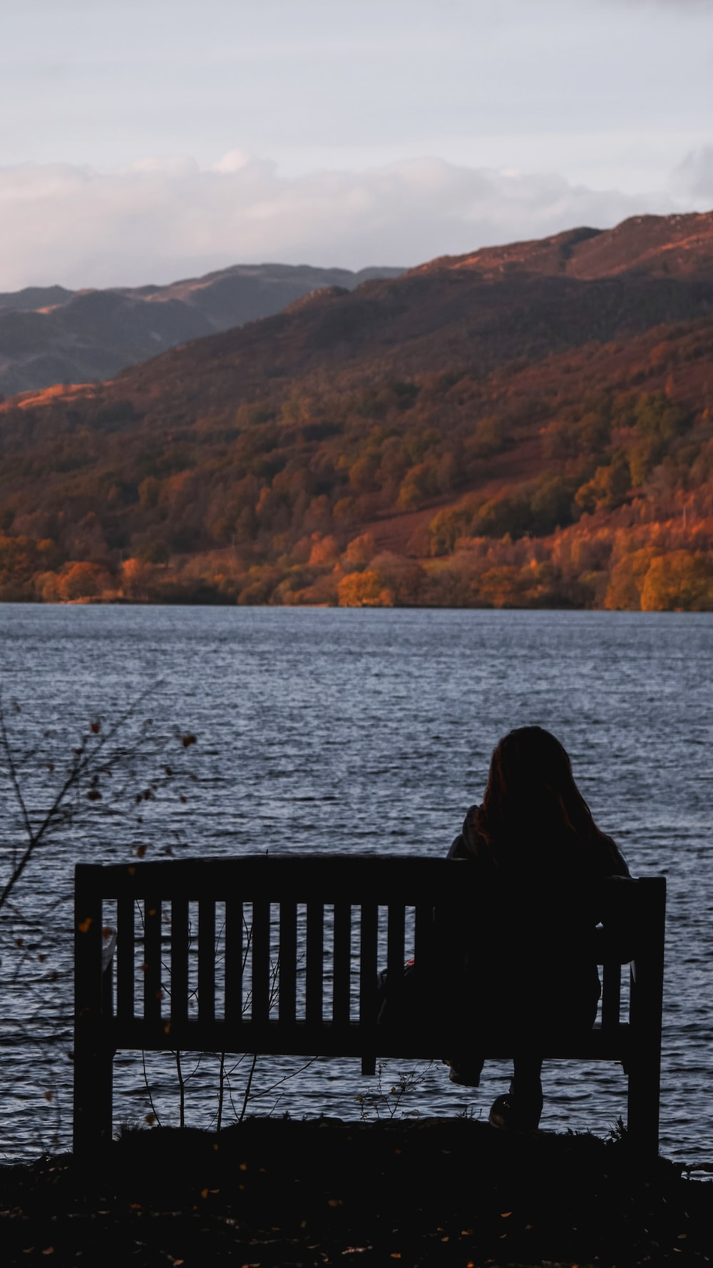 person sitting on black wooden bench near body of water during daytime