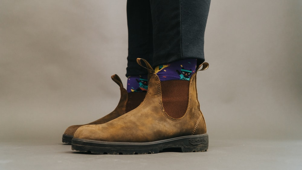 person wearing brown and black boots