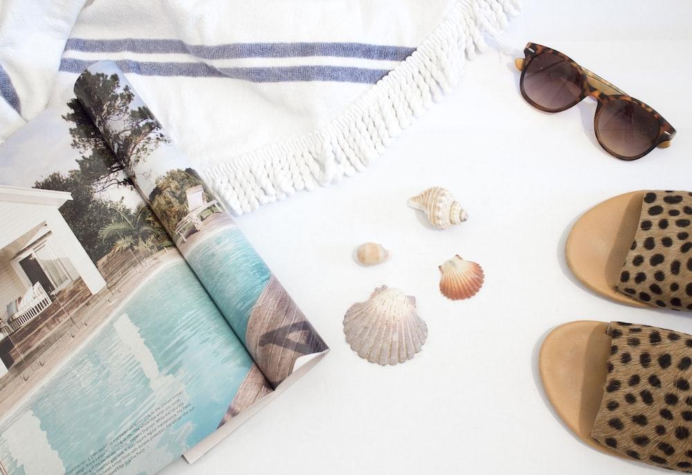 opened magazine beside seashells, slide sandals, sunglasses and towel on white surface
