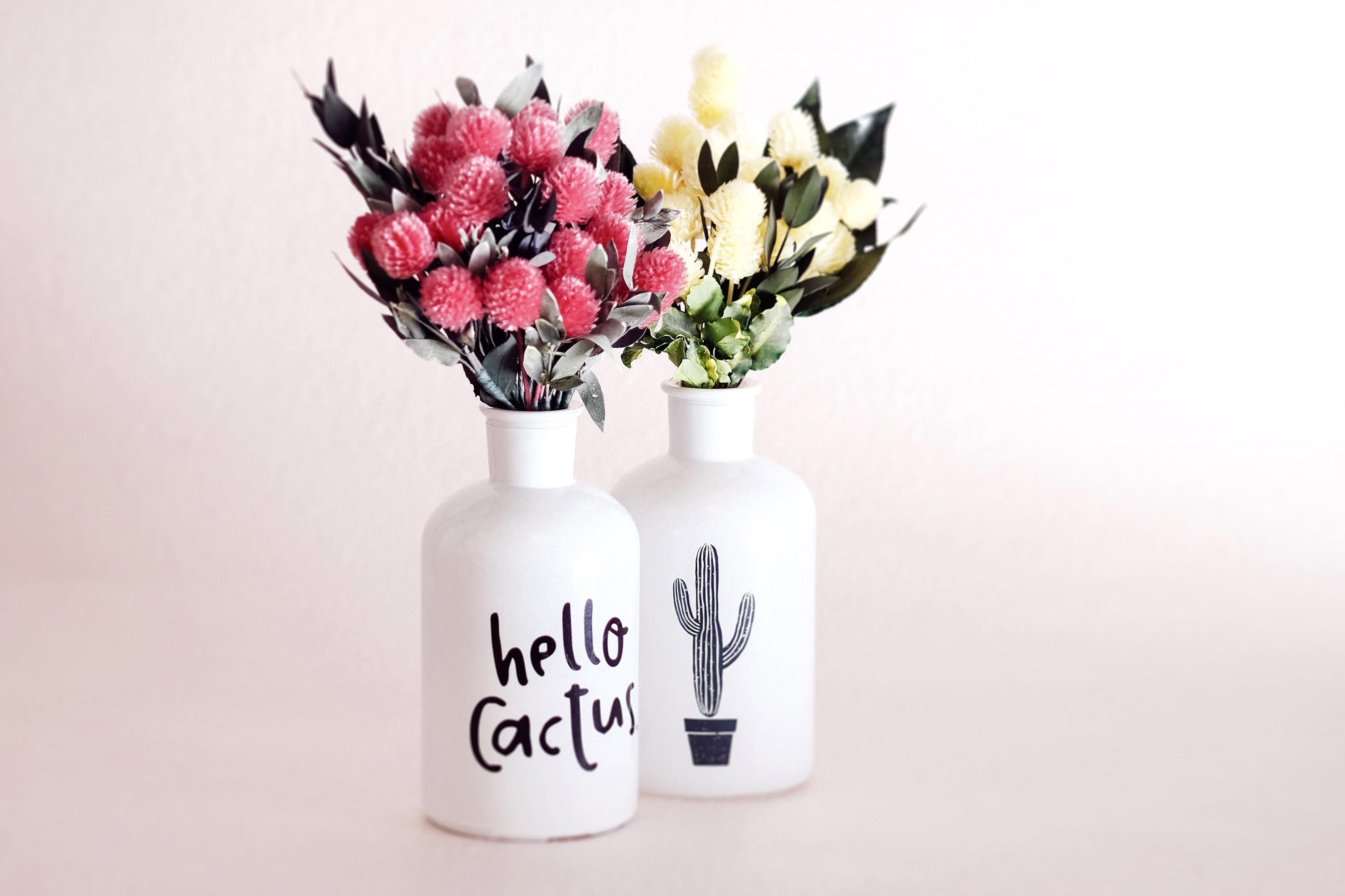 assorted flowers in white ceramic vases