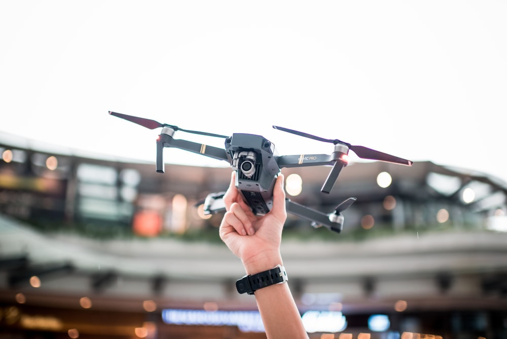 selective focus photography of person holding gray Mavic Pro drone