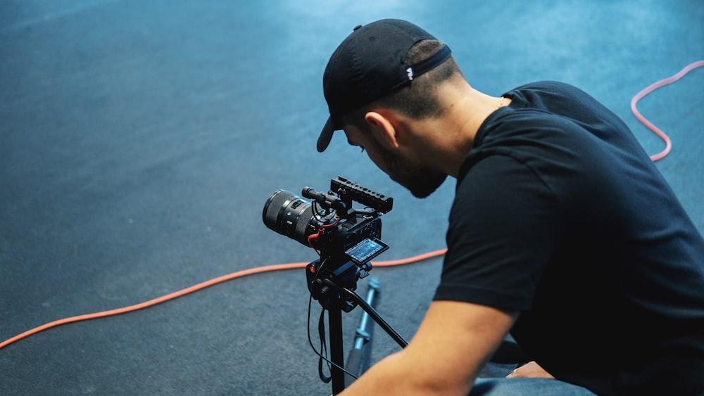 man wearing black shirt near black DSLR camera