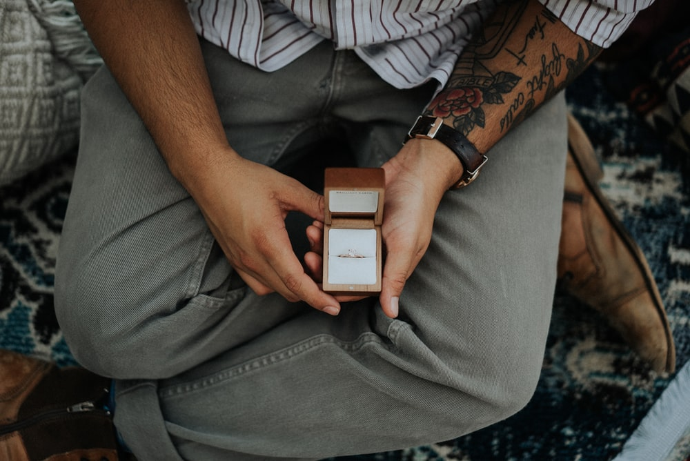 person holding opened brown ring box
