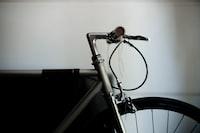 black road bicycle beside wall