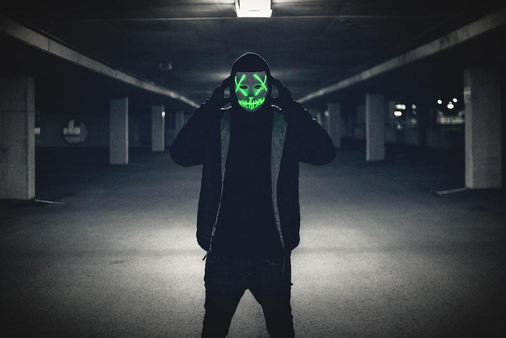 man wearing black jacket and red LED mask