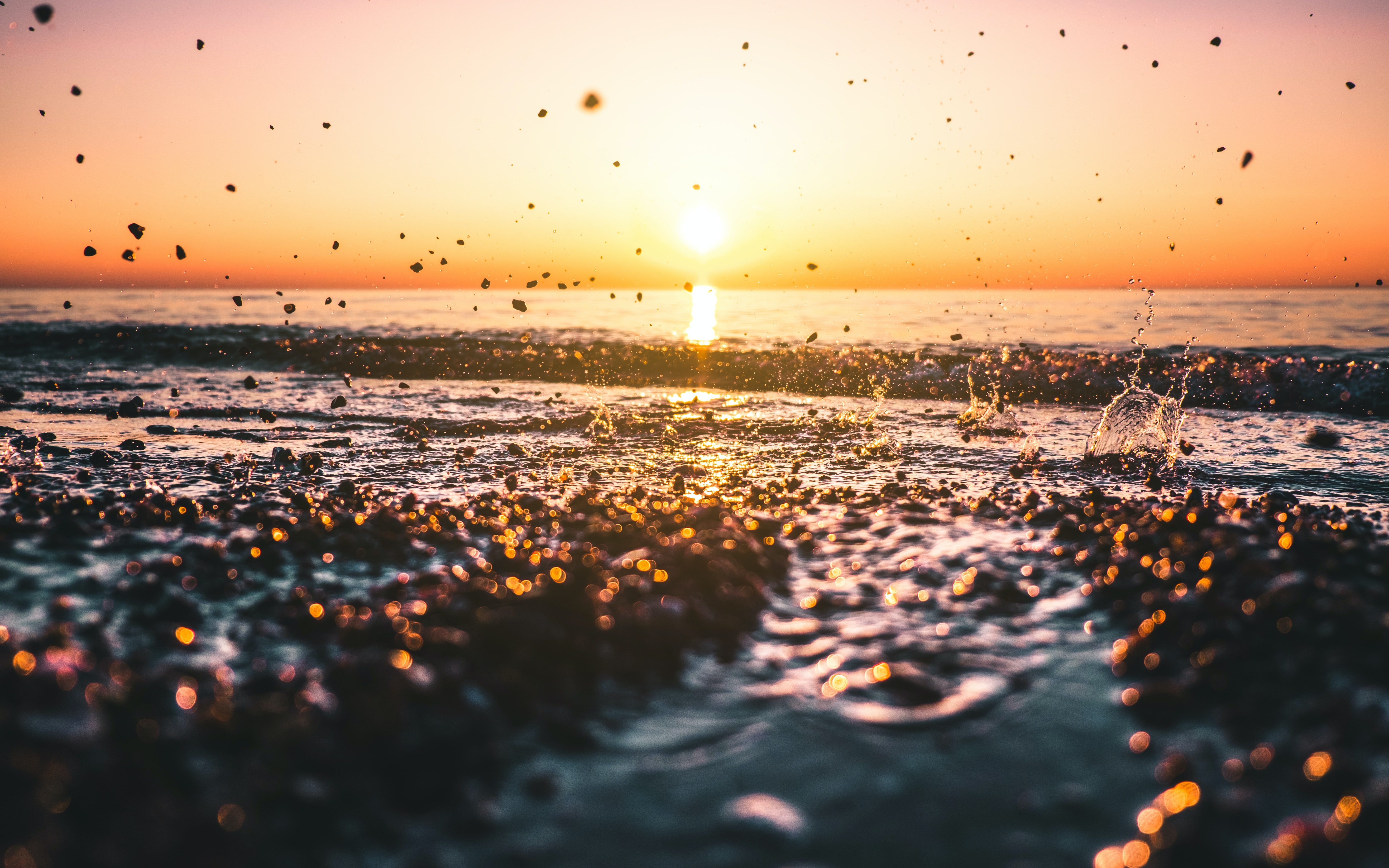 rocks being thrown on the water during sunset