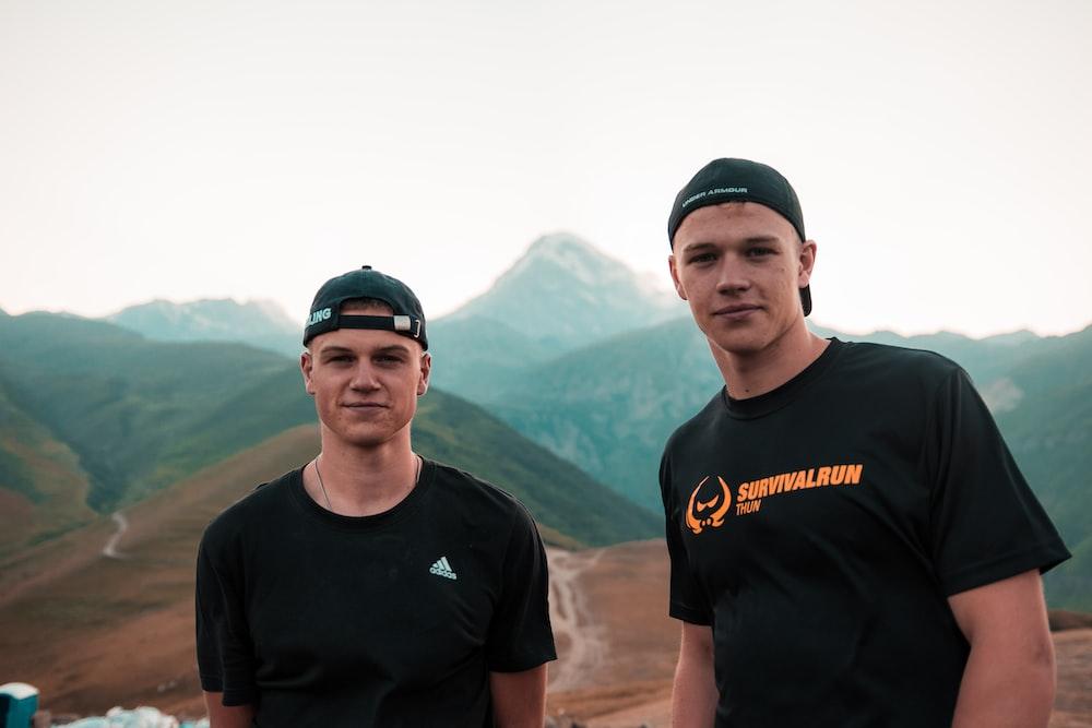 two men standing on landscape field