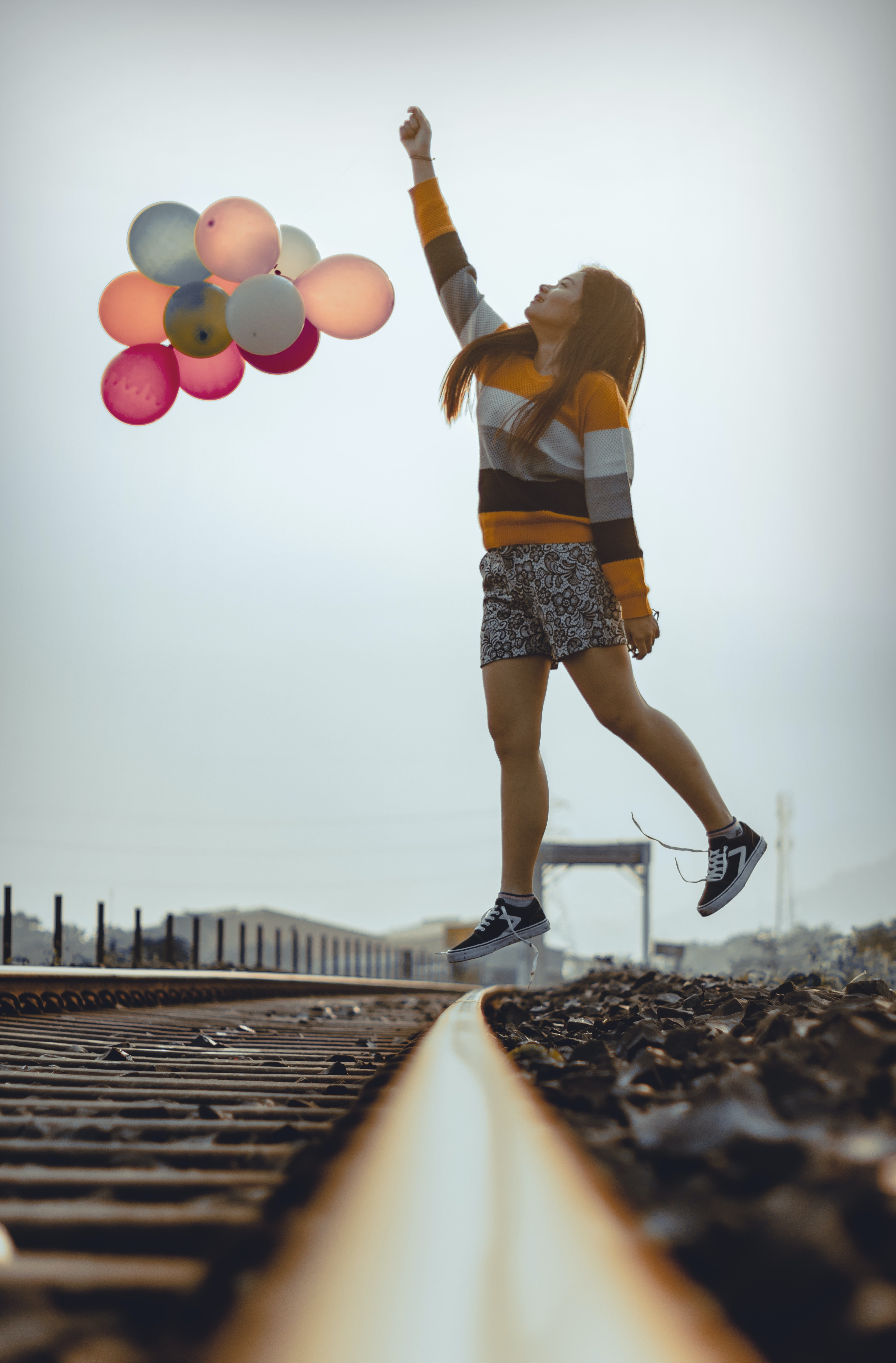 woman holding balloons while jumping on train railways