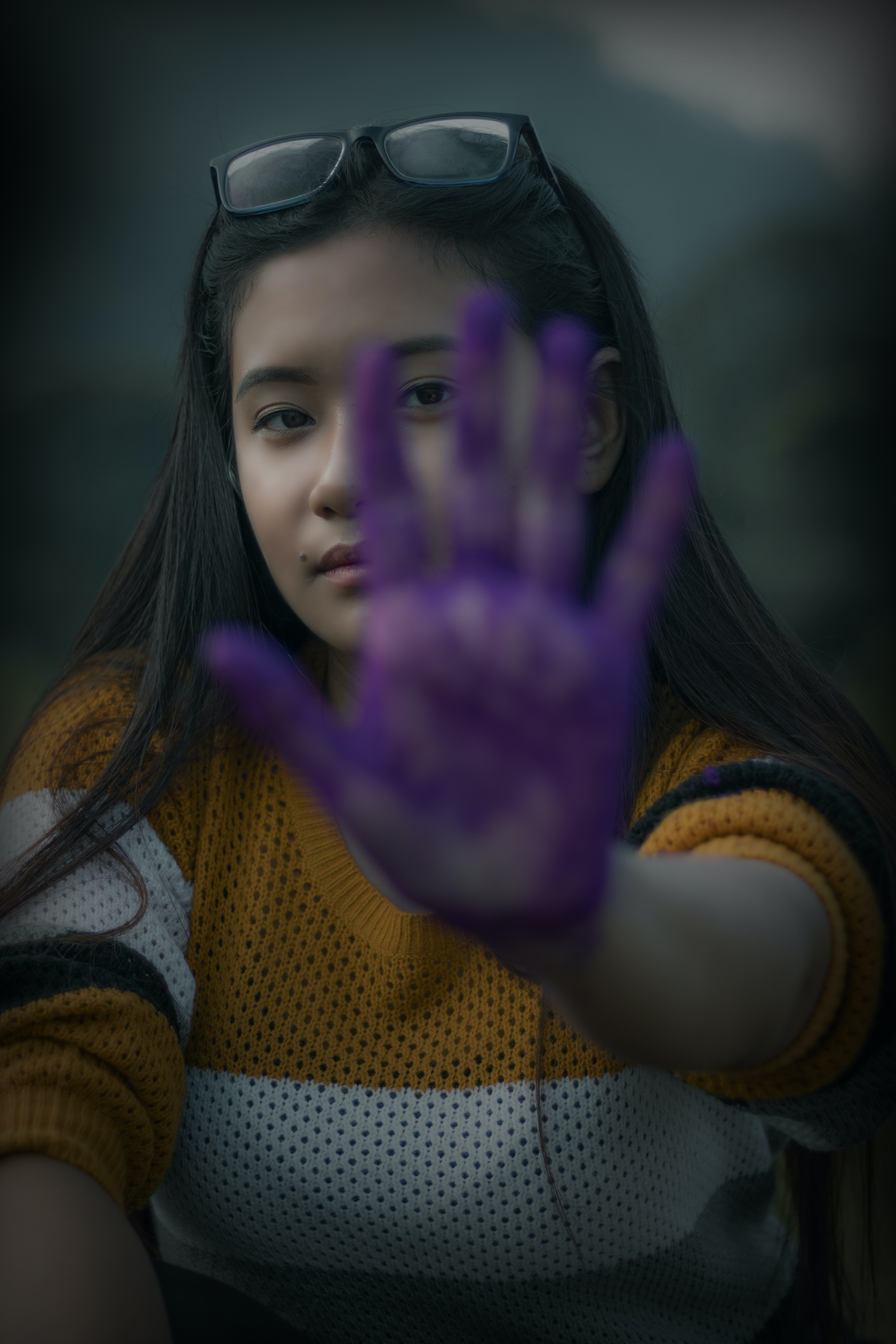 woman showing her left hand with purple paint