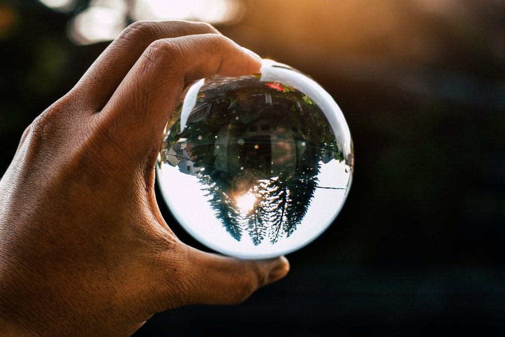 person holding water globe