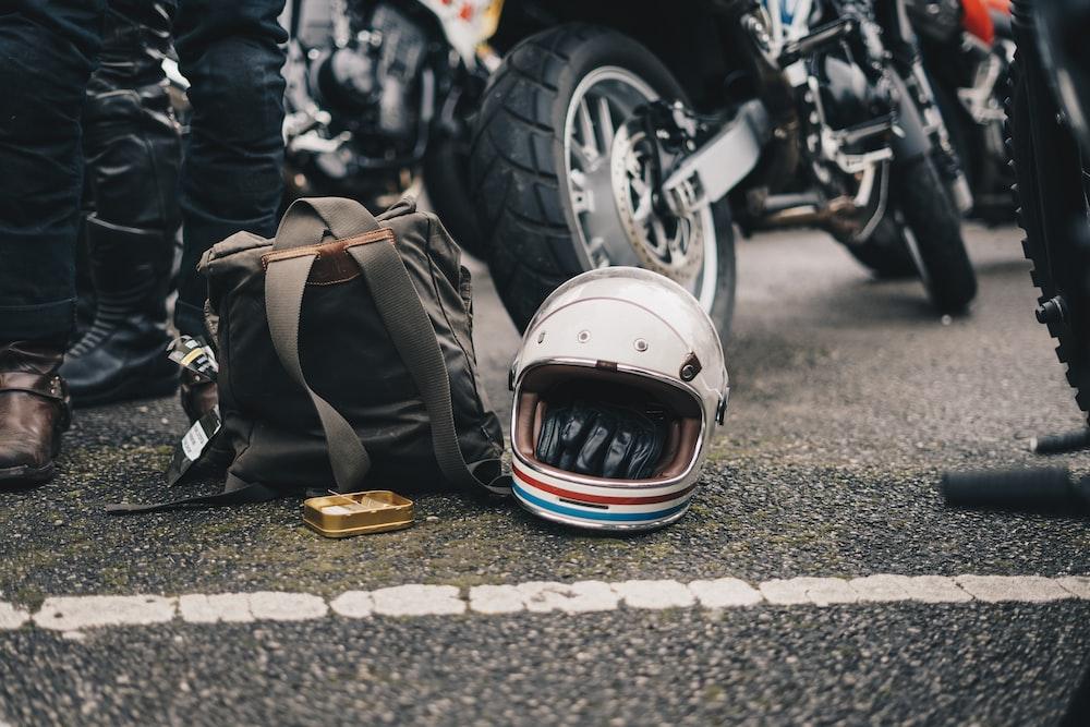 white helmet beside black backpack on road