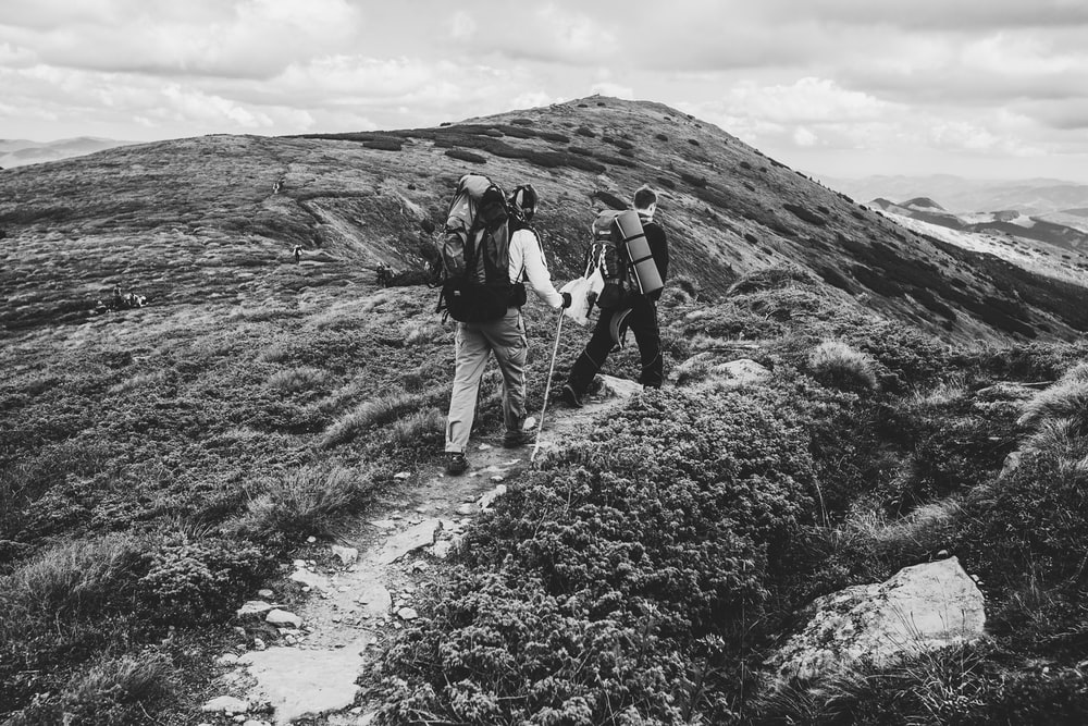 two people walking on mountain in grayscale photography