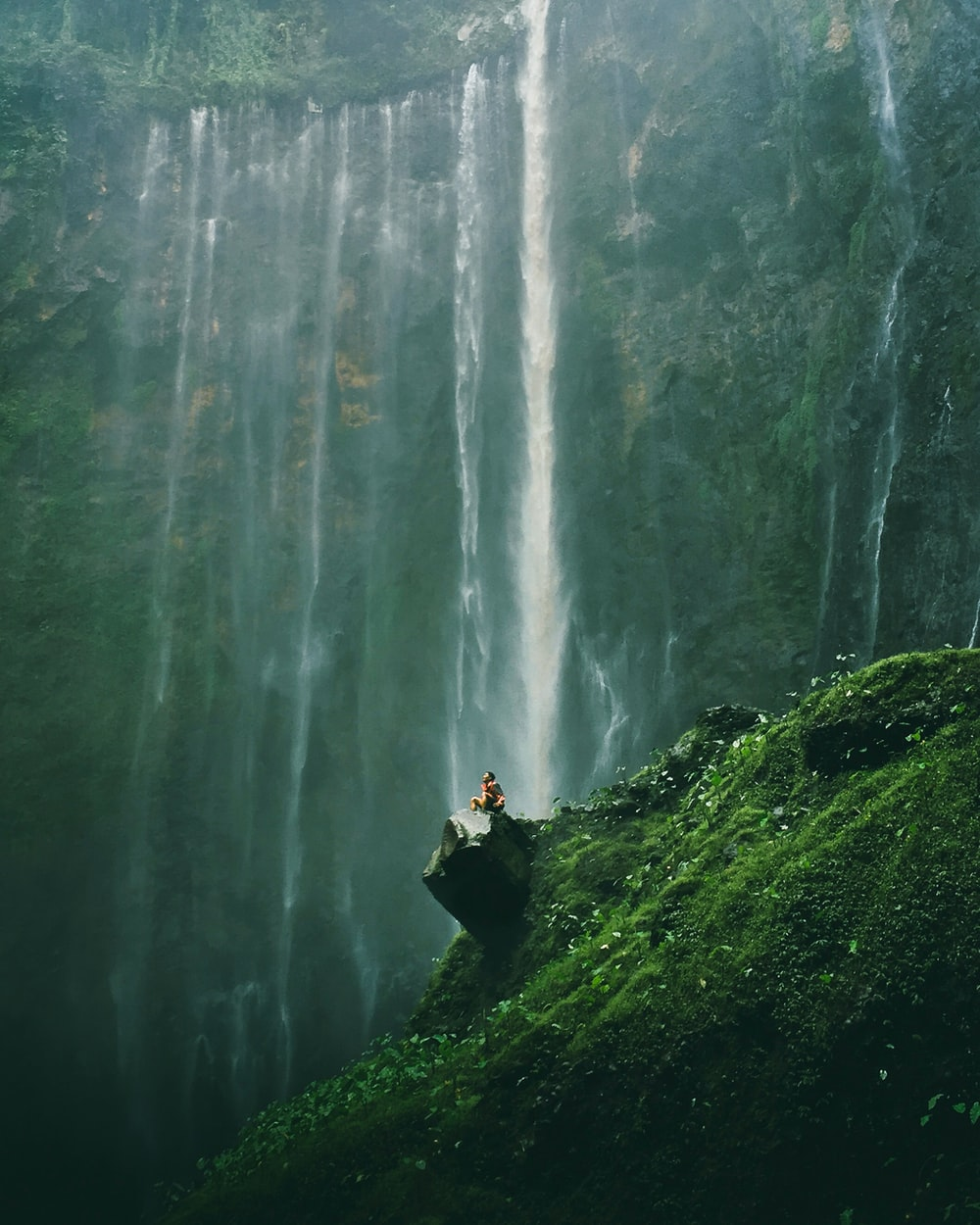 aerial photography of person sitting on rocks near waterfalls