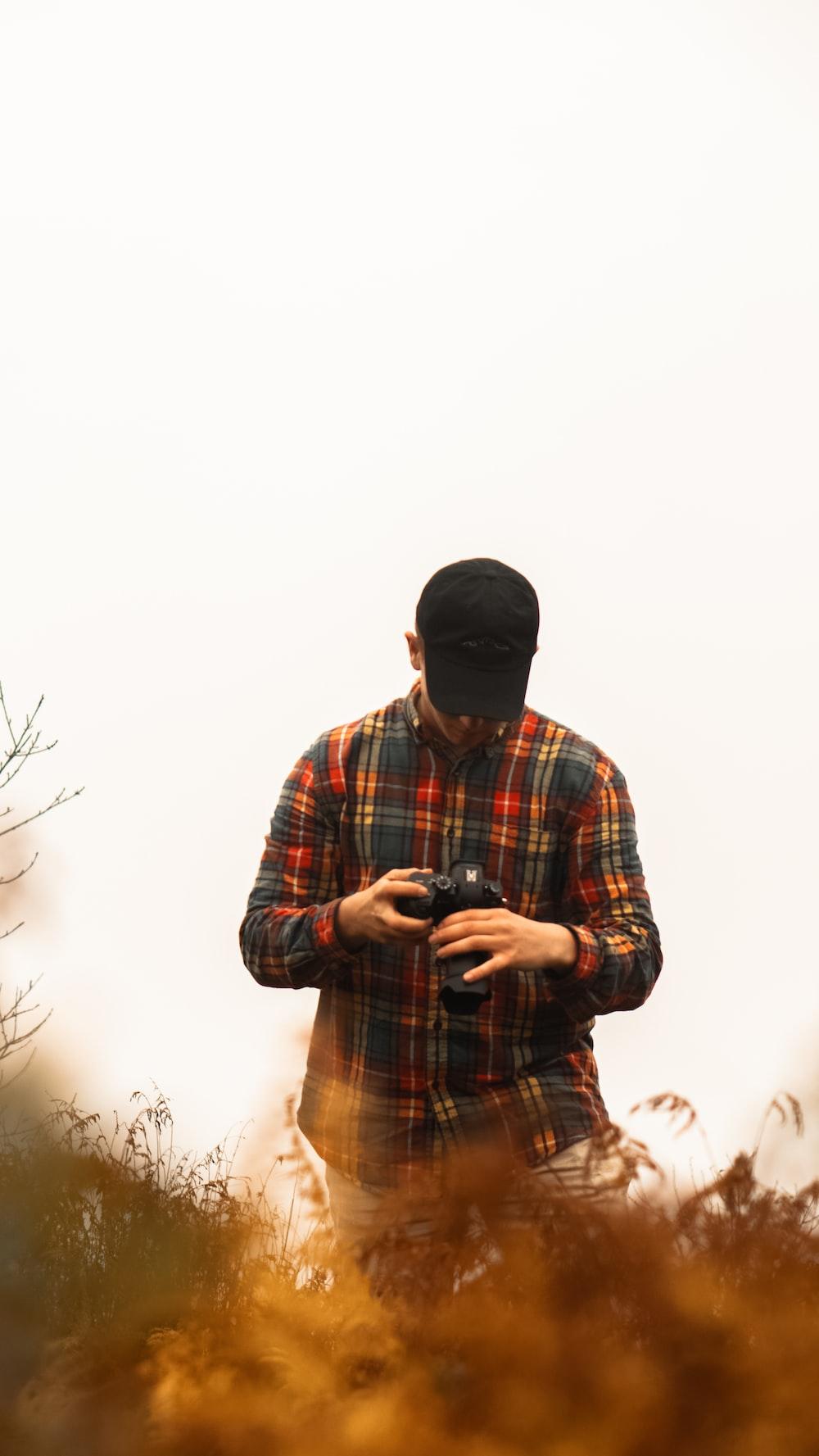 man looking at DSLR camera